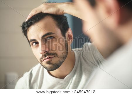 Latino Person With Beard Grooming In Bathroom At Home. White Metrosexual Man Worried For Hair Loss A