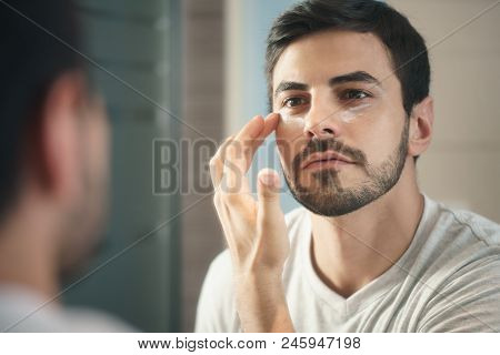 Young Hispanic People And Male Beauty. Metrosexual Man Applying Lotion For Anti-aging Treatment Arou