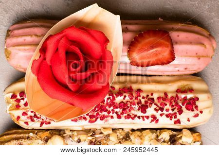 Sweet Delicious Colorful French Eclairs Decorated With Marzipan Red Rose. Group Of French Dessert. E