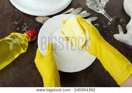 Women's Hands In Gloves Wash Dishes With Detergent, On Black