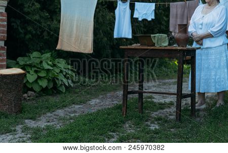 An Old Woman Stands And Waits, In White Vintage Clothes, In The Courtyard, Near The Table. On The Ta