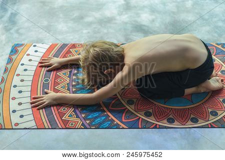 High Angle View Of Little Kid Practicing Yoga In Extended Child Utthita Balasana Pose