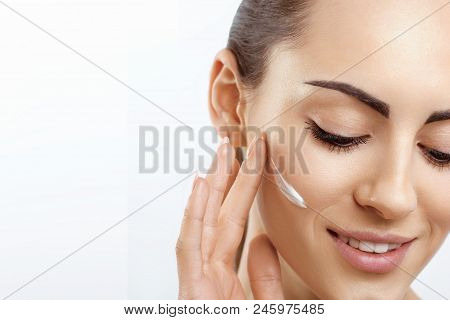 Facial Care. Female Applying Cream And Smiling.portrait Of  Young Woman With Cosmetic Cream On Skin.