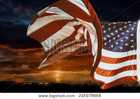American Flag Waving In The Wind Beautiful Fiery Orange Dramatic Sunset And Sunrise Sky.