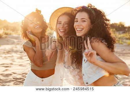 Picture of gorgeous young caucasian and african american women 20s in stylish clothing laughing and showing peace sign at camera during summertime near ocean poster