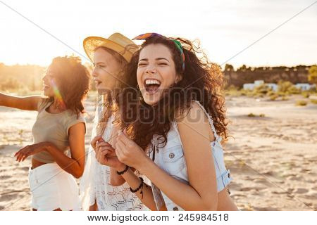 Image of three joyous multiethnic girls 20s in stylish clothing laughing and enjoying summertime during beach party at seaside