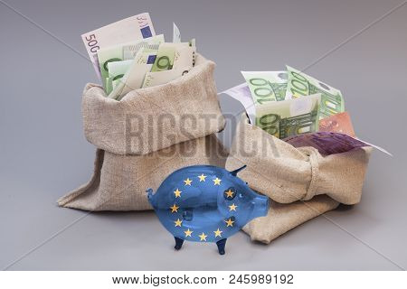 Two Money Bag With Euro And Glass Piggy Bank With Flag Of European Union On Gray