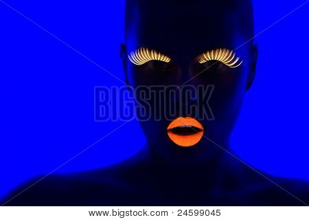 close-up portrait of young woman wearing UV lashes and lipstick under blacklight poster