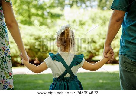 Family, Parenthood, Adoption And People Concept. Happy Mother, Father And Little Girl Walking In Sum