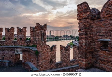 Sunset in Adige river, in Verona, Veneto, Italy. Photo taken from the Castel Vecchio Bridge (or Scaliger Bridge), a medieval fortified bridge, in the old town. poster