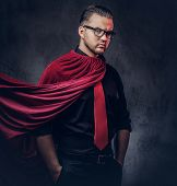 Portrait of a genius villain superhero in a black shirt with a red tie. Isolated on a dark background. poster