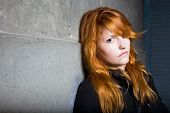 Scared and lonely moody portrait of a beautiful fashionable young redhead girl. poster