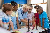 Teacher teaching children math on abacus. Mature mathematics teacher helping schoolchildren use wooden abacus. Group of multiethnic kids understanding maths in classroom. poster