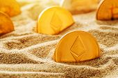 Golden ethereum in sand, conceptual image for lost and found valuable cryptocurrency coins that are standing the test of time. poster