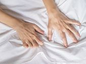 Hand clutches grasps a white crumpled bed sheet in a hotel room, a sign of ecstasy, feeling of pleasure or orgasm. Orgasm is the greatest point of sexual pleasure or a climax of sexual excitement poster