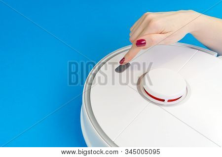 Robot Vacuum Cleaner Isolated On Blue Background, Close Up Photo