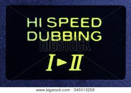 Macro close up photograph of vintage tape machine hi speed dubbing function indicator light.