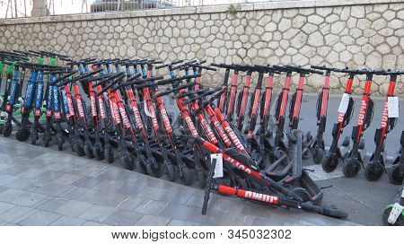 Row Of Electric Scooters For Rent On Pavement In Malaga, Spain