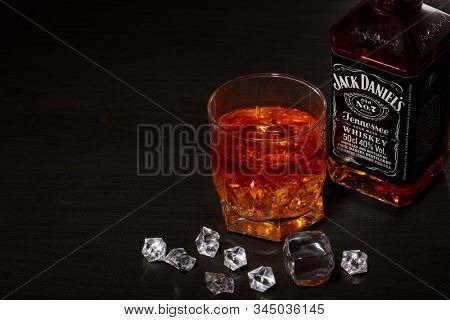 St.Petersburg, Russia - December 2019 - Bottle of Jack Daniel's whiskey and glass with drink and ice  on wooden table on brown background. Brand of the American whiskey
