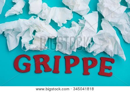 a pile of used tissues and the word grippe, flu written in italian, on a blue background