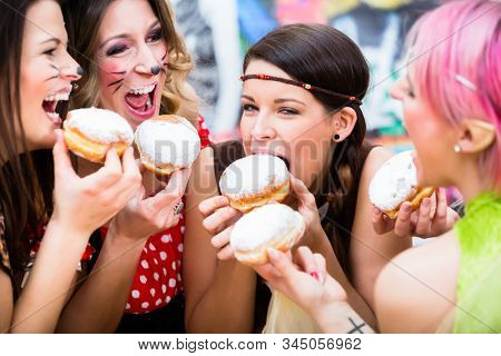 Happy girls at German Fasching Carnival eating doughnut-like traditional pastry