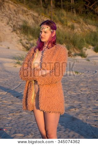 Young Seminude Girl In  Sweater Posing At The Beach. Sexy Woman Outdoors At Sunset