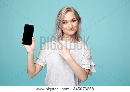 Cheerful Female Person In The T-shurt Pointing Phone In The Blue Studio.