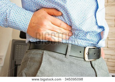 Man Holds His Hand In Area Of Right Lower Quadrant Of Abdomen Or Bottom Of Abdomen On Right In Appen