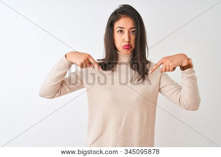 Beautiful chinese woman wearing turtleneck sweater standing over isolated white background Pointing down looking sad and upset, indicating direction with fingers, unhappy and depressed.
