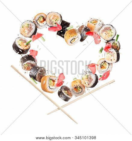 Sushi Rolls With Chopsticks Frozen In The Air In The Shape Of The Heart