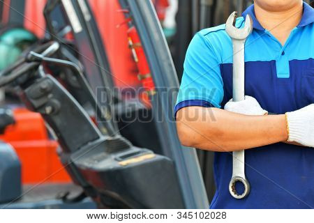 Car Mechanic Wearing A Dark Blue Uniform Stand Holding Wrench On Blur Forklifts Background,copy Spac