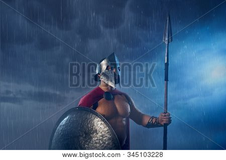 Portrait Of Spartan Warrior Standing Outdoors With Spear And Shield In Evening. Front View Of Muscul