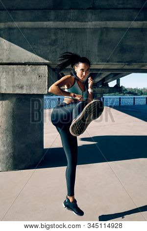 Young Sporty Woman Doing High Kick Outdoors. Young Female Athlete Demonstrates Kickbox. Stretching A