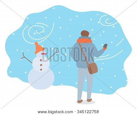 Winter Snowstorm And Bag Weather Conditions Outdoors. Man Wearing Warm Clothes Passing Snowman With