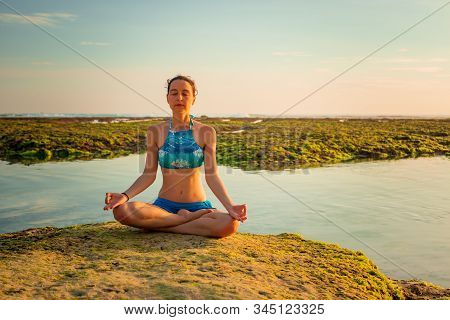 Young Woman Meditating, Practicing Yoga And Pranayama At The Beach. Sunset Yoga Practice. Hands Rais