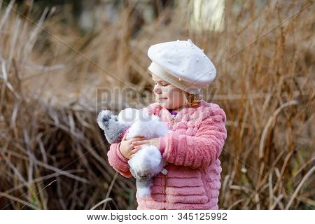 Outdoor Portrait Of Little Cute Toddler Girl In Pink Coat And White Fashion Hat Barret Playing With