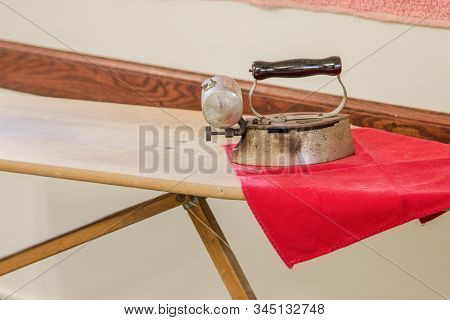 Antique Iron And Ironing Board. Old Fashioned Metal Clothes Iron On Wooden Ironing Board In Horizont