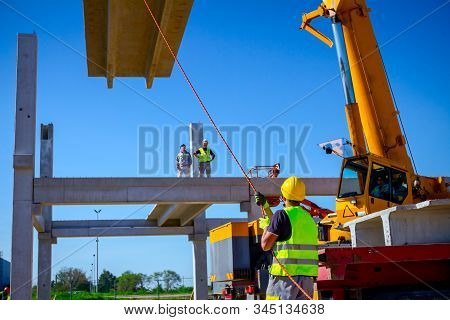 Worker Is Helping Mobile Crane With Rope To Manage Concrete Joist For Assembly Huge Construction.
