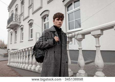 European Young Man In A Trendy Gray Plaid Coat With A Stylish Hairstyle With A Leather Black Backpac