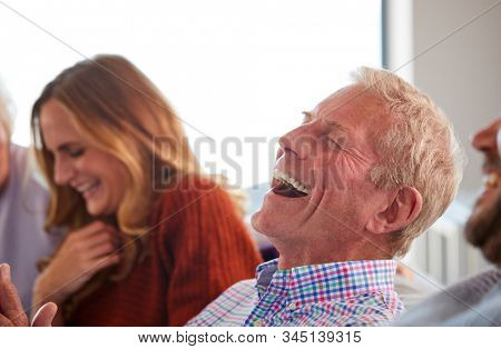 Senior Parents With Adult Offspring Sitting On Sofa At Home Talking And Laughing