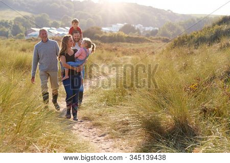 Multi-Generation Family Walking Along Path Through Sand Dunes Together