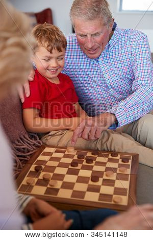Grandparents Playing Board Game Of Draughts With Grandchildren At Home
