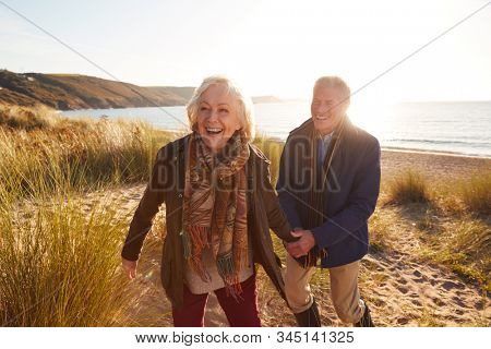 Loving Active Senior Couple Holding Hands As They Walk Through Sand Dunes Against Flaring Sun