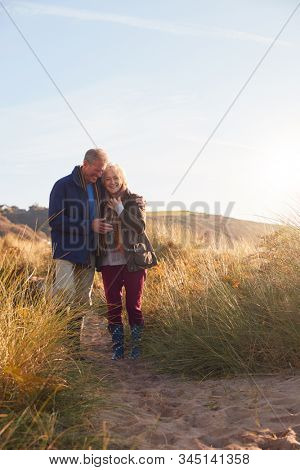 Loving Active Senior Couple Hugging As They Walk Through Sand Dunes