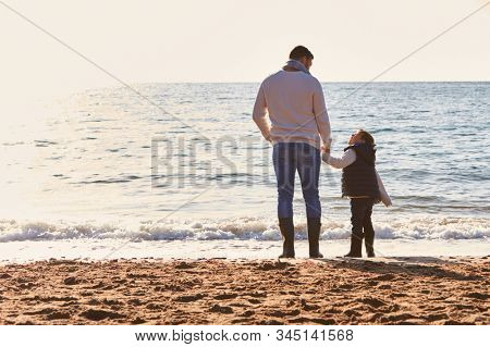 Rear View Of Father With Son Looking Out To Sea Silhouetted Against Sun