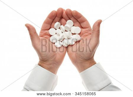 Man hand with handful of big white pills isolated on white background. White shirt, business style. Medicament and food supplement for health care. Pharmaceutical industry. Pharmacy.