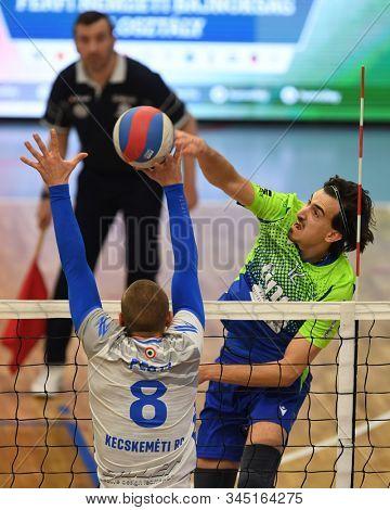 KAPOSVAR, HUNGARY – JANUARY 12, 2020: Kristof Horvath (r) strikes the ball at a Hungarian National Campionship volleyball game between Kaposvar (blue) and Kecskemet (white) in Kaposvar Arena, Kaposvar
