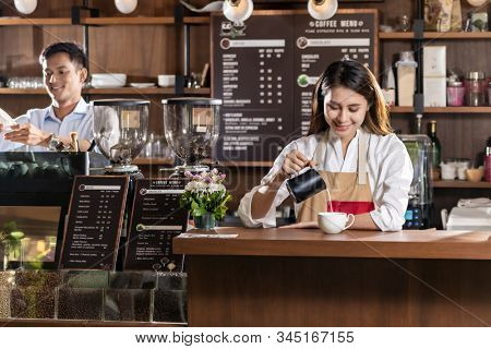 Young adult asian female barista pouring fresh milk to prepare latte coffee for customer in cafe bar.