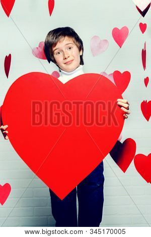 ?ute pre-teen boy holding big heart surrounded by little hearts. First love. Valentine's Day.