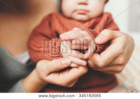 Young Mother Holding The Handles Of Her Little Daughter, Close-up, Little Fingers, Concept Of Mother